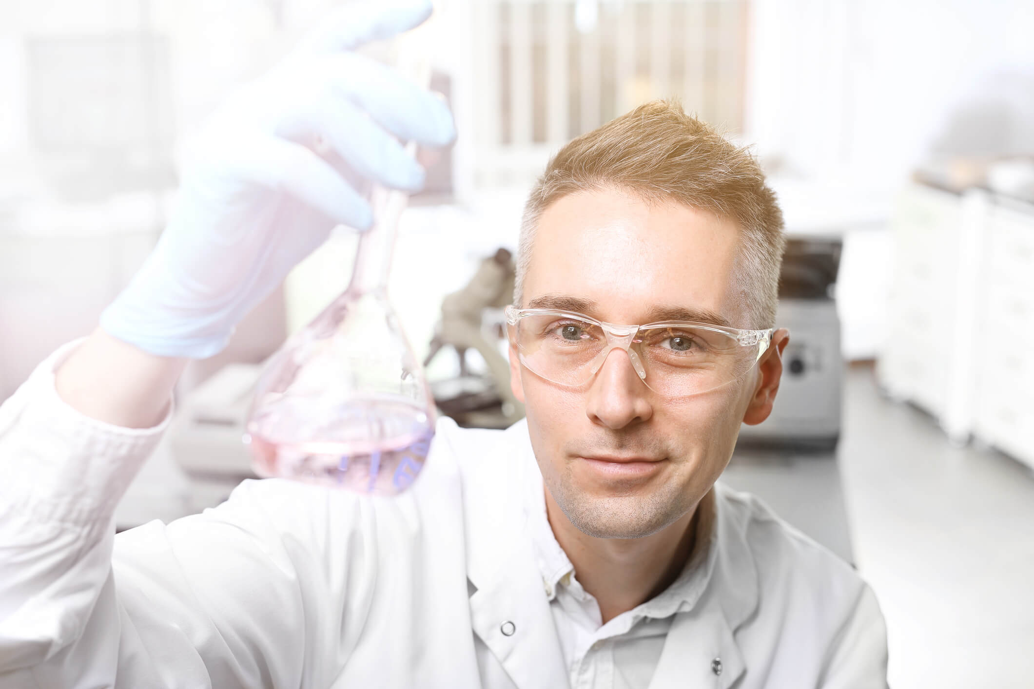 Lab man holding test tube with solution
