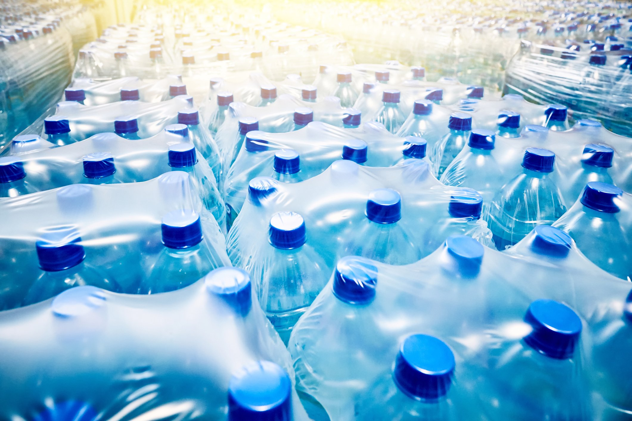 Many packaged blue mineral water bottles