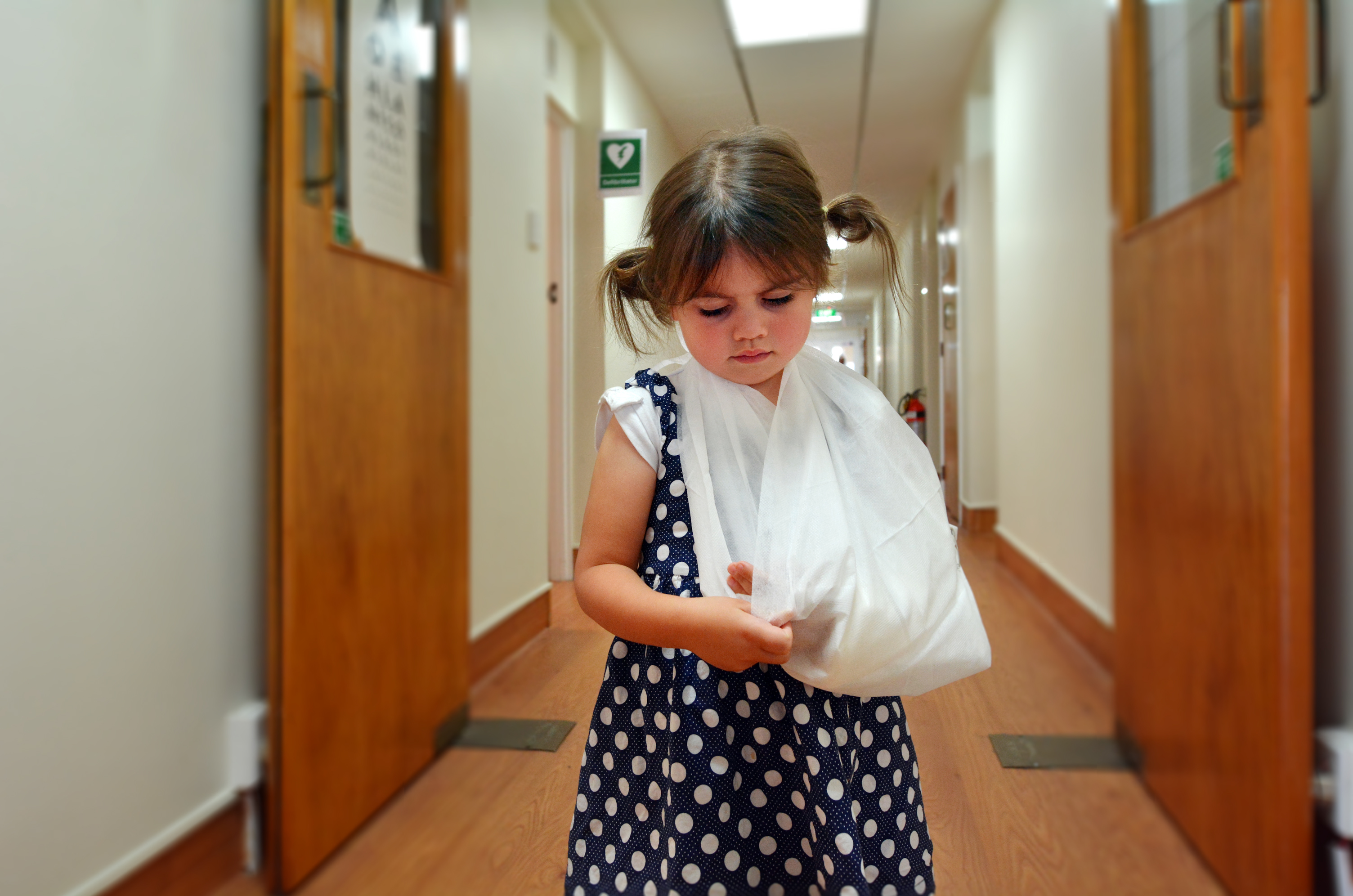 Sad little girl with a broken arm in hospital corridor.