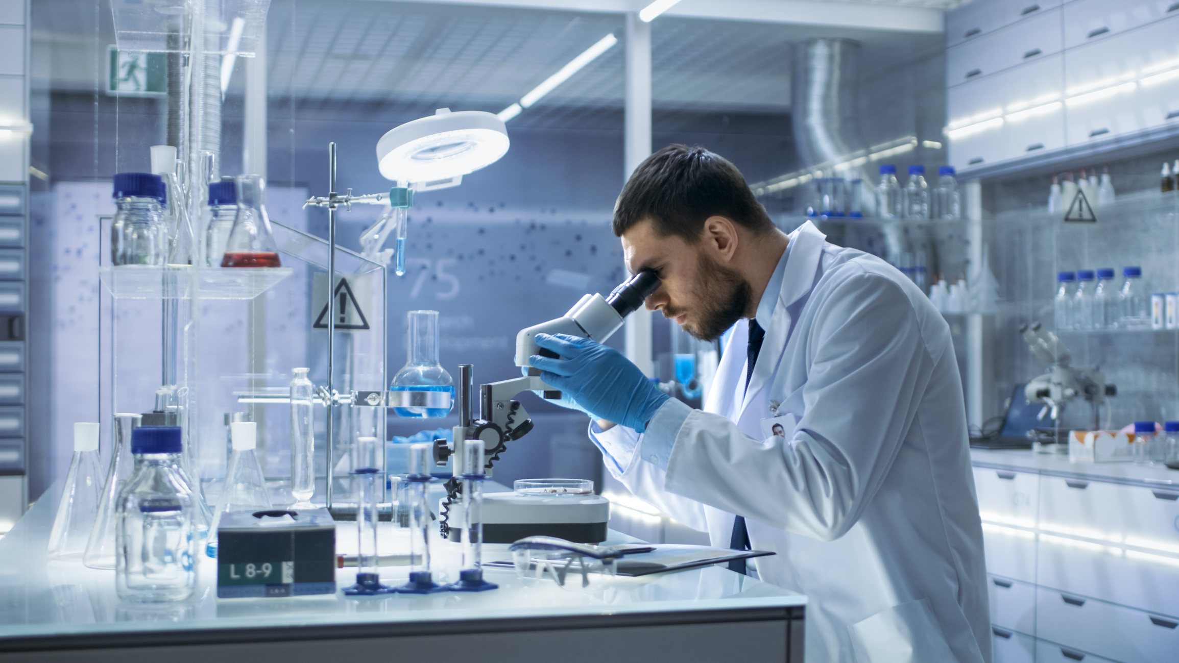 Research Scientist Looks into Microscope. He's Conducts Experiments in Modern Laboratory.