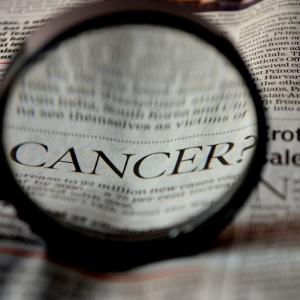 Newspaper clipping with magnifying glass on cancer