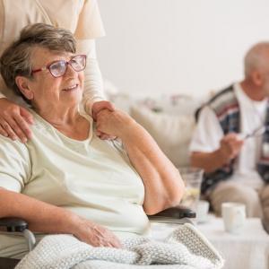 Happy senior lady sitting at wheelchair in nursing home for elderly