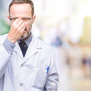 Middle age senior hoary professional man wearing white coat over isolated background tired rubbing nose and eyes feeling fatigue and headache. Stress and frustration concept