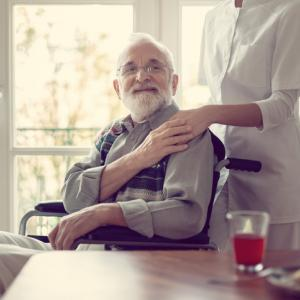 Senior patient in nursing home with helpful nurse in white uniform