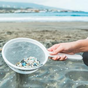 Young woman cleaning microplastics from sand on the beach - Environmental problem, pollution and ecolosystem warning