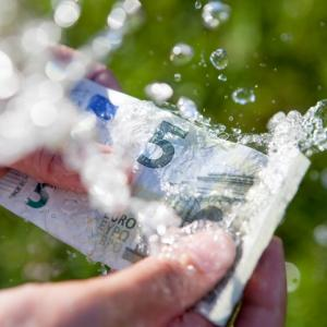 Two hands washing 5 euro banknote clean