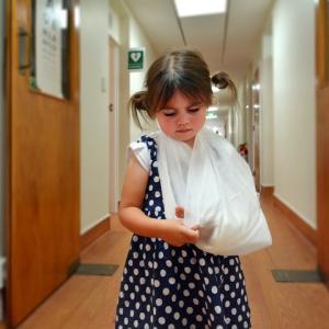 Sad little girl with a broken arm in hospital corridor