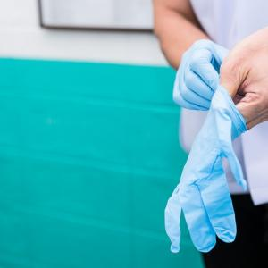 wearing sterile gloves to preparation for treatment