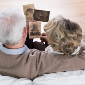 Senior marriage sitting on the sofa and looking at old photos