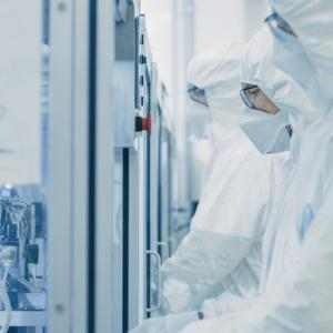 On a Factory Team of Scientists in Sterile Protective Clothing Work on a Modern Industrial 3D Printing Machinery. Pharmaceutical, Biotechnological and Semiconductor Creating / Manufacturing Process