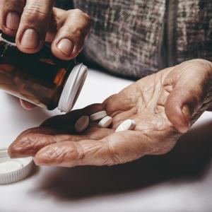 Close-up image of senior woman taking out pills from the pills bottle. Focus on hands. Old female taking medicines.